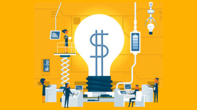 Image of a giant light bulb with a dollar sign being worked on by people in a lab.