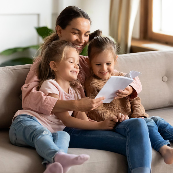 Image of a mom reading book to two girls.