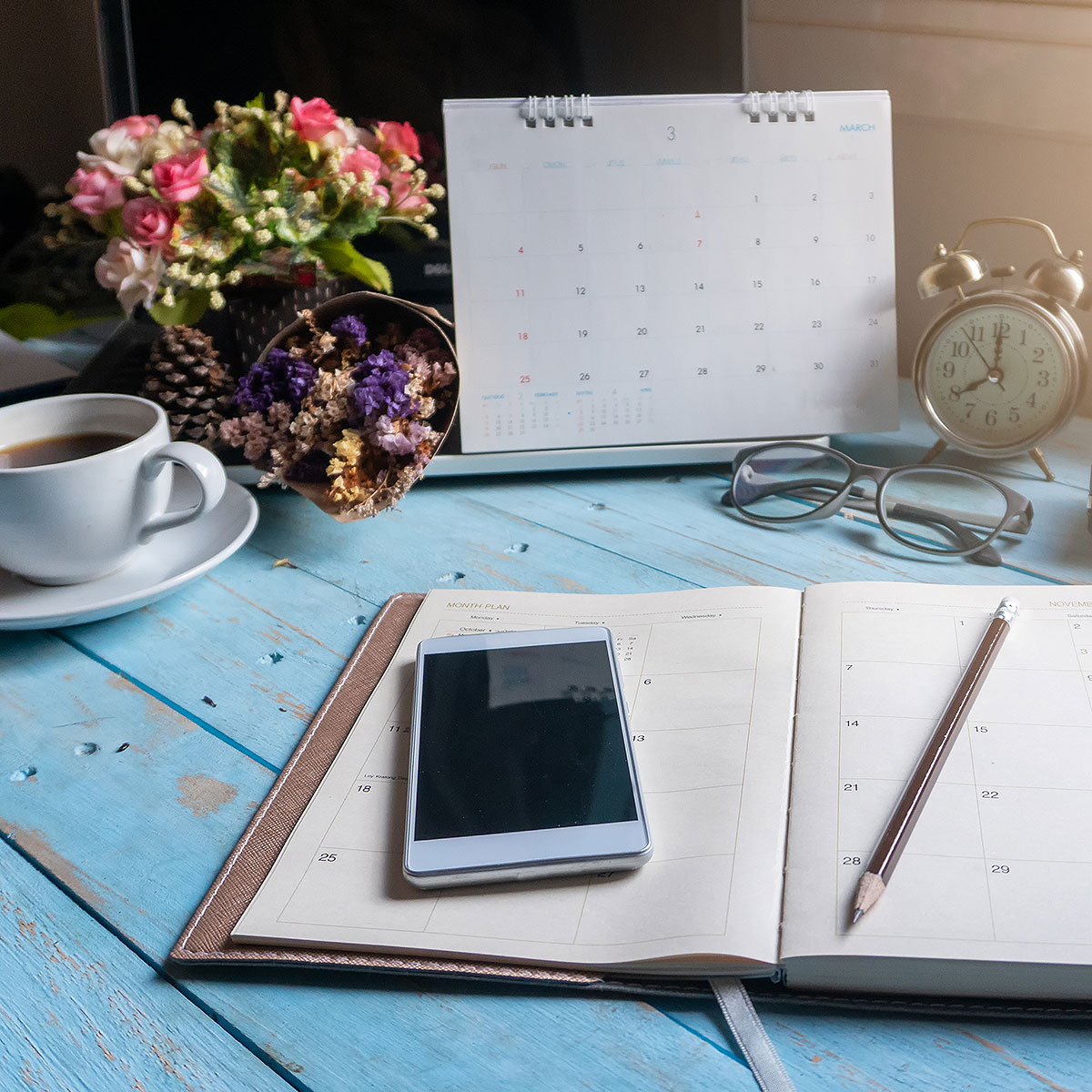 Phone, calendar and a planner on a desk of someone planning to hangout with their friends