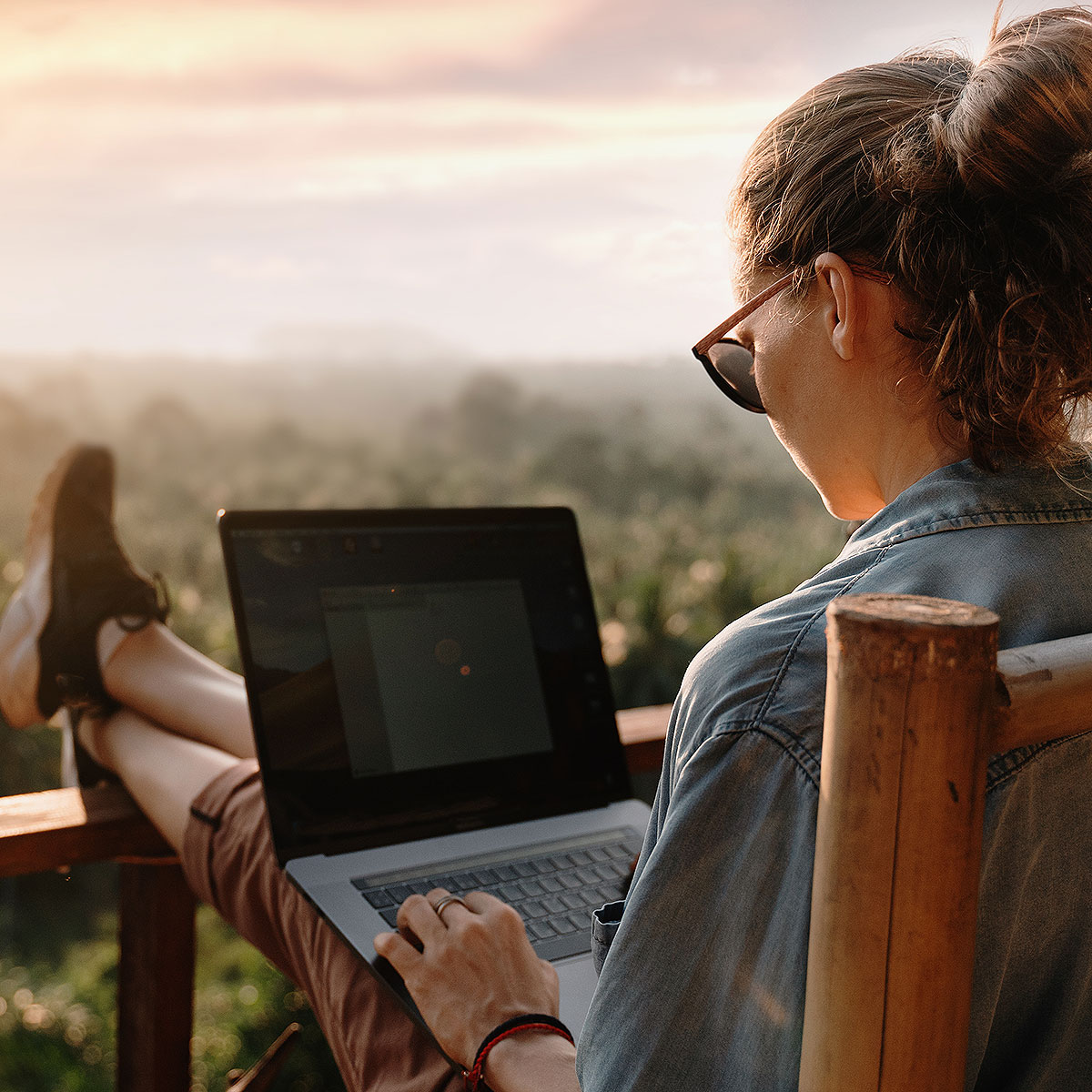 image of woman working on laptop with a scenic view