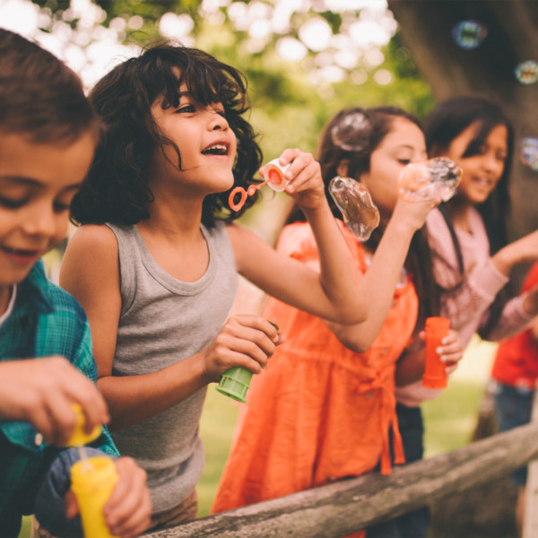 Image of kids blowing bubbles outside.