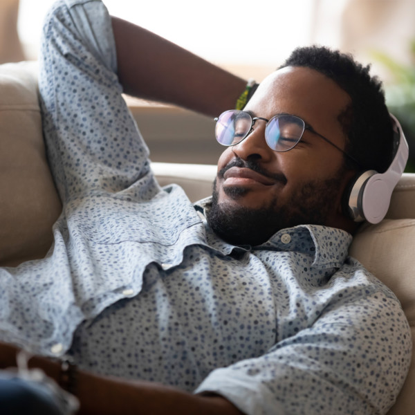 Image of someone on the couch with headphones on.
