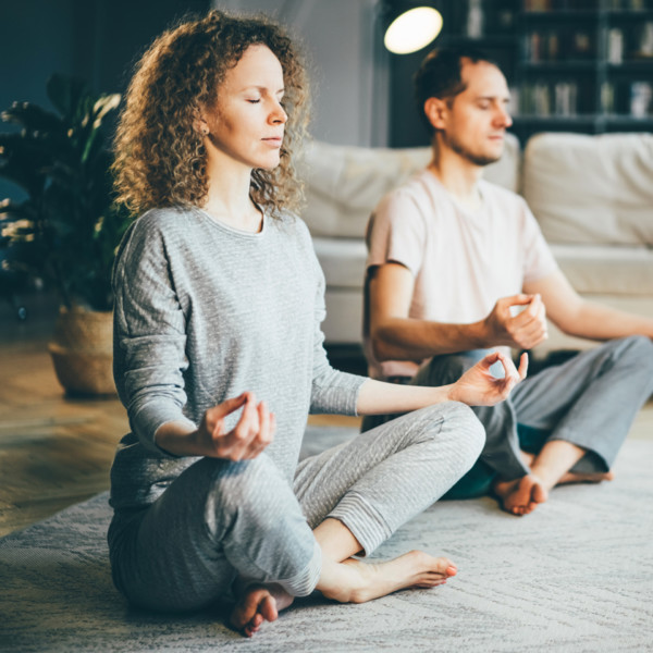 Couple meditating in living room