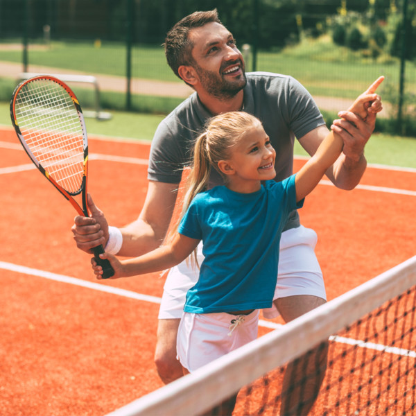 ad teaching his daughter how to play tennis