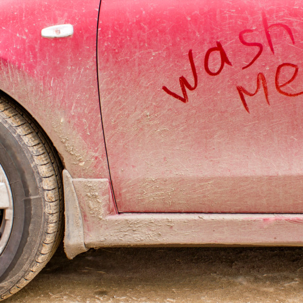 """Car covered in dirt with """"wash me"""" written in the dirt"""
