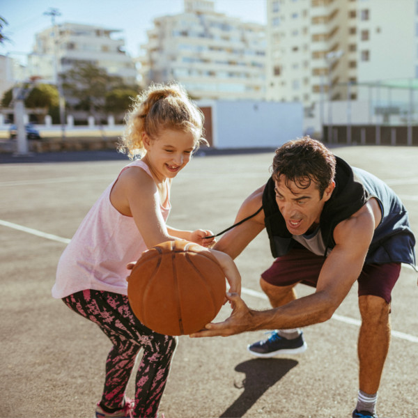Image of father and daughter playing basketball together