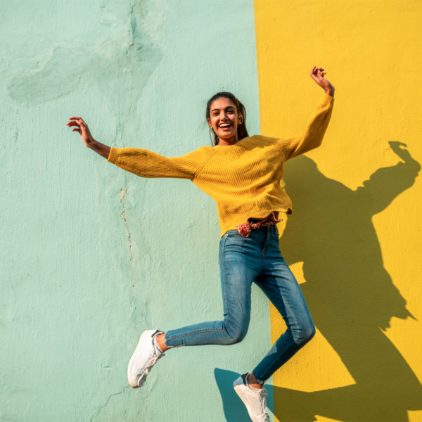 Image of someone jumping in front of a green and yellow wall.
