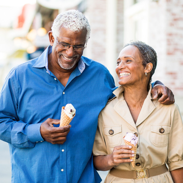 Image of an older couple on a date walking with ice cream.