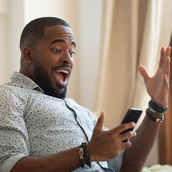 Man receiving good news from cell phone