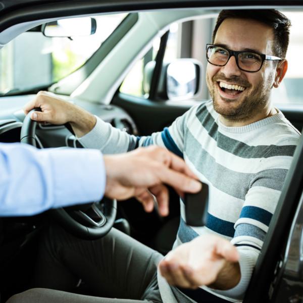 Man smiling while receiving keys to car
