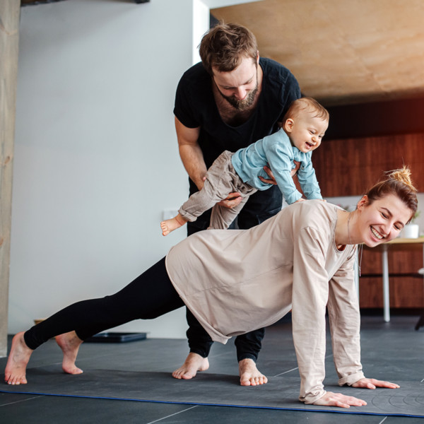 Mom doing yoga while dad plays with baby