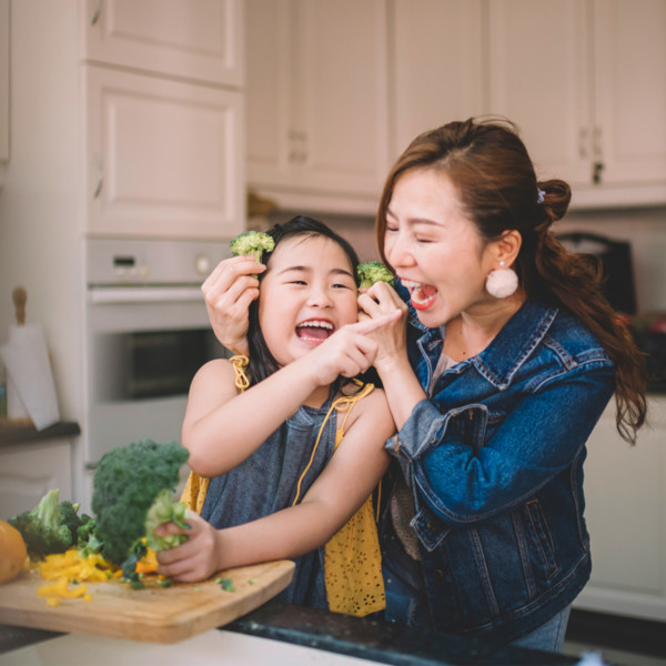 Mother and daughter eating broccoli in the kitchen