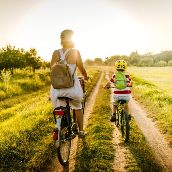 Mother and son riding bikes through grass