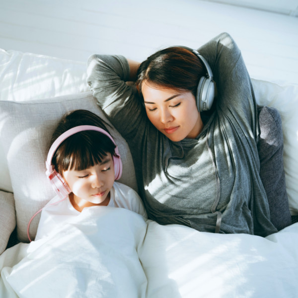 Image of a mother and daughter relaxing together with headphones on.
