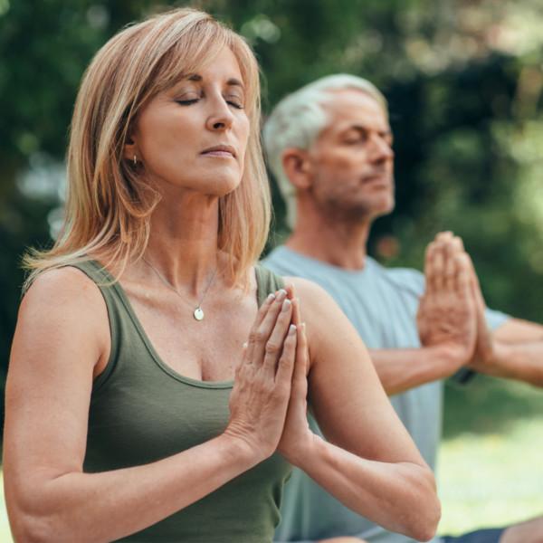 Older couple doing yoga outside