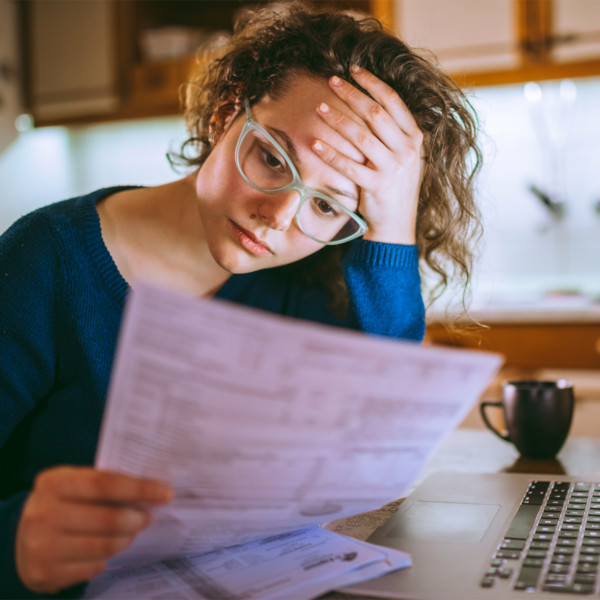 woman stressed from reviewing debt papers as she tried to manage debt