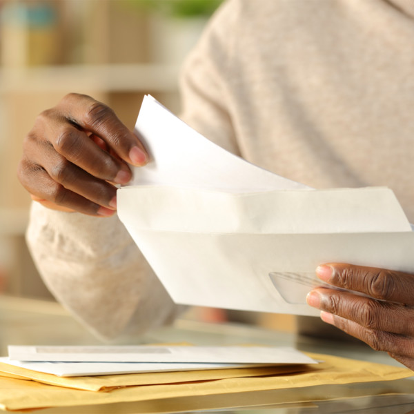 woman mailing an envelope to help manage debt