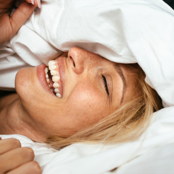 Woman smiling in bed under the covers