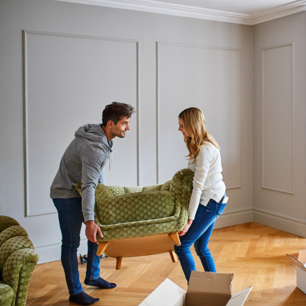 Image of man and women moving a green chair