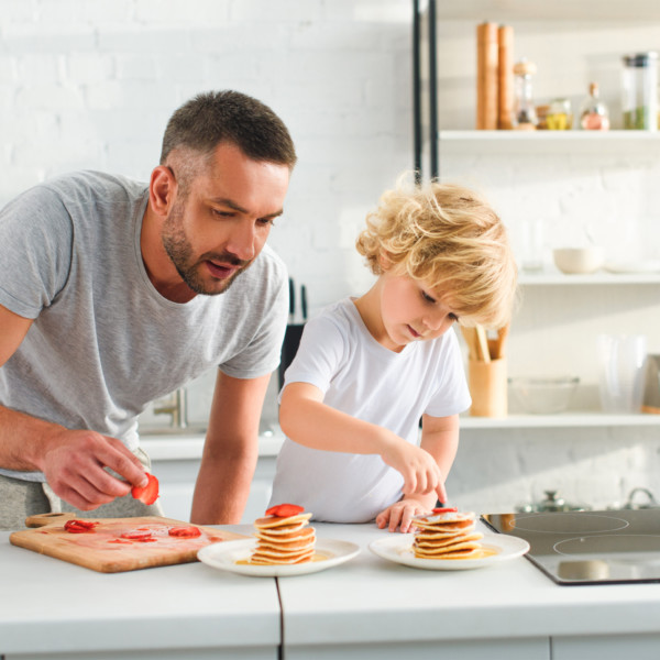 Image of father and son cooking pancakes in white kitchen
