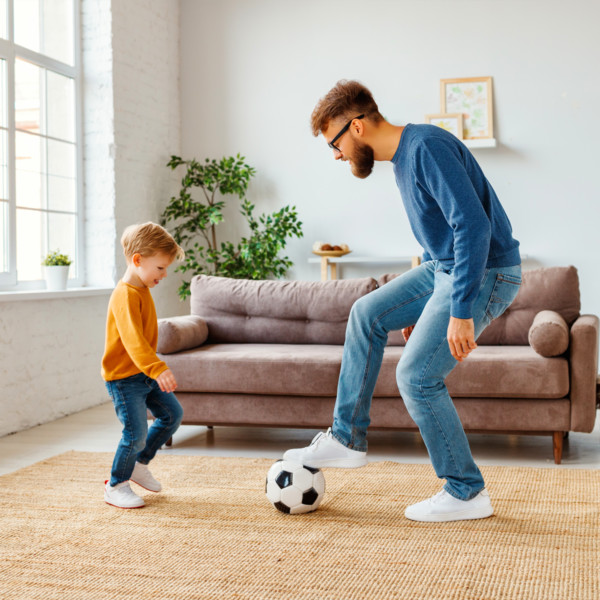Image of father and son playing soccer in living room