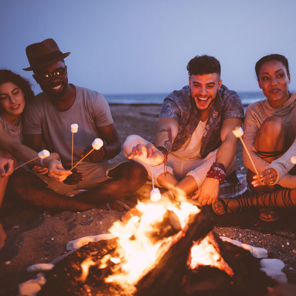 Image of friends roasting marshmallows on a fire
