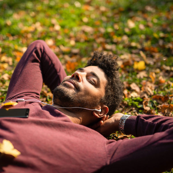 Image of someone laying in the grass listening to music