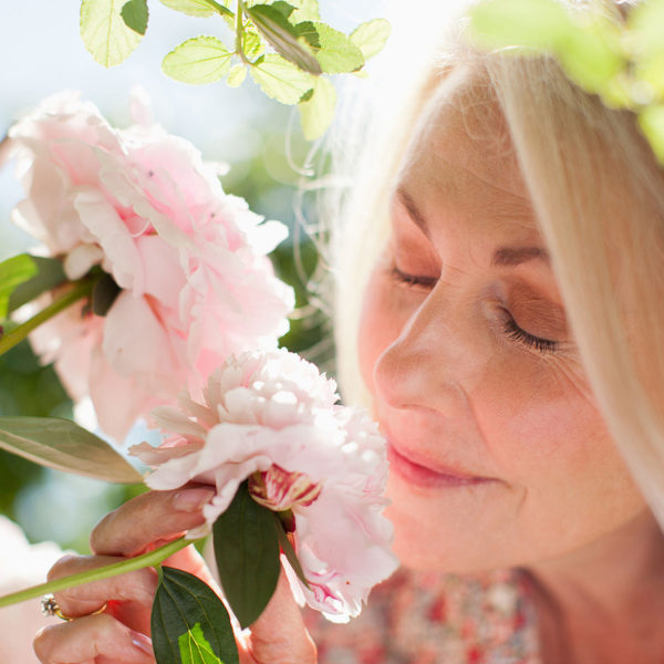 Image of a woman smelling flowers