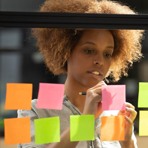 Image of someone writing on sticky notes