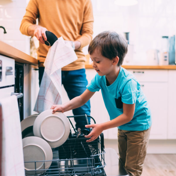 Image of a child with their parent, washing dishes.