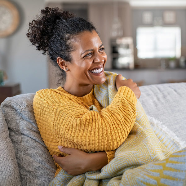 image of a woman smiling on a couch covered in a blanket