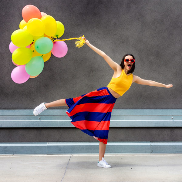 Image of a woman holding colorful balloons