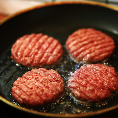 Image of burgers being cooked in a pan