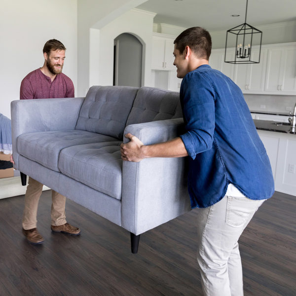 Friend giving his friend a hand moving a couch