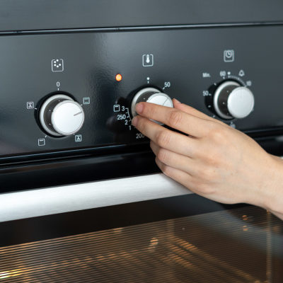 Turning the stove to a higher temperature to cook chicken and rice