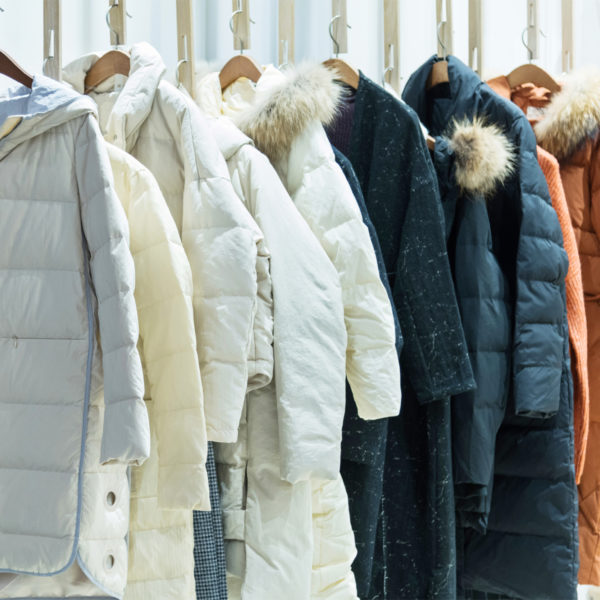 Winter coats hanging on a clothing rod as part of a capsule wardrobe