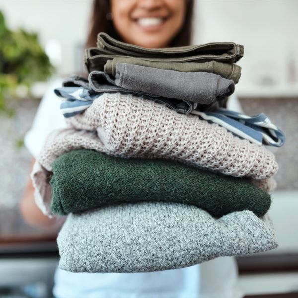 Woman holding stack of clothing for her capsule wardrobe
