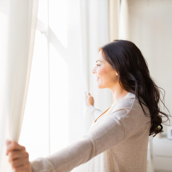 Woman opening up curtains to get ready for work from home