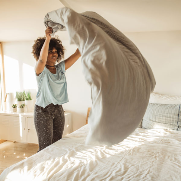 Woman in work from home fashion setting up her bed
