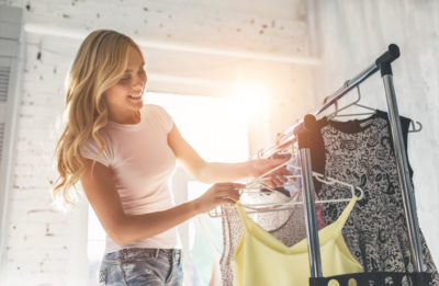 Woman hanging shirt on rack to create a capsule wardrobe