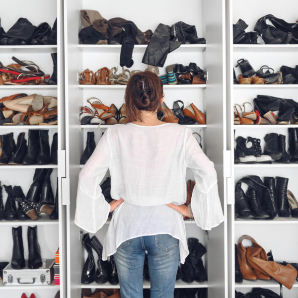 Woman standing in front of disorganized wardrobe in need of a capsule wardrobe